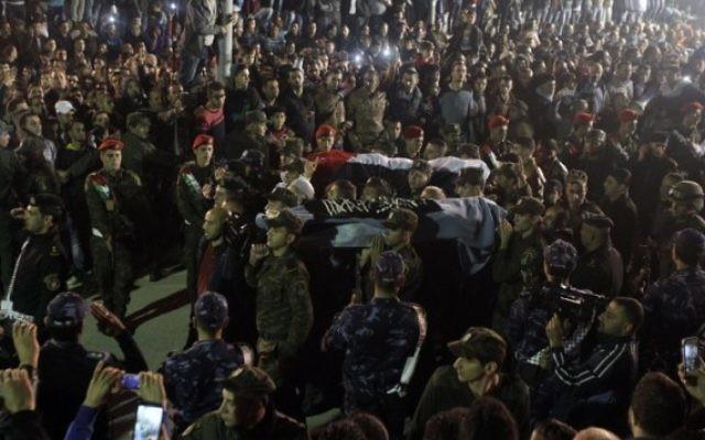 Les forces de sécurité de l'AP portent à Hébron les corps de deux des cinq terroristes Palestiniens restitués par Israël le 30 octobre 2015. Ils ont été tués dans des attaques au couteau contre des Israéliens (Crédit : Hazem Bader/ AFP)