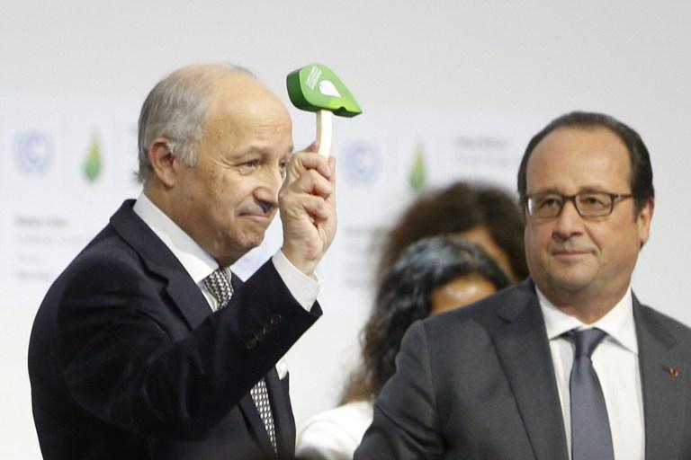 Le ministre des Affaires Etrangères et envoyé du président pour la COP21 Laurent Fabius (gauche) montre le marteau officiel de la conférence climatique, pendant que le président Francois Hollande le regarde, après l'adoption d'un accord historique sur le climat, le 12 décembre 2015. (Crédit : François Guillot/AFP)