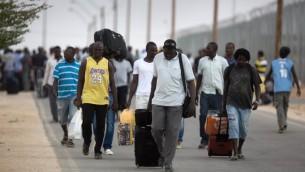 Des migrants clandestins africains portent leurs biens après leur libération du centre de détention de Holot dans le désert du Néguev en Israël, le 25 août, 2015. (Crédit photo: Menahem Kahana / AFP)
