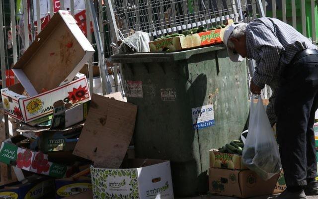 Un vieil homme cherchant parmi les ordures près du marché dans la ville israélienne de Petah Tikva,  le 24 juin 2015 (Crédit : Nati Shohat / Flash90)