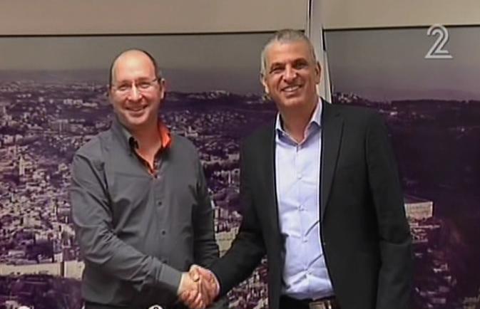 Le dirigeant du syndicat de travailleur Histadrut Avi Nissenkorn (gauche) et le ministre des Finances Moshe Kahlon (droite) se serrent la main le 21 décembre 2015, lors de discussions destinées à éviter une grève générale pour une augmentation des salaires dans le service public. (Crédit : capture d'écran Deuxième chaîne)