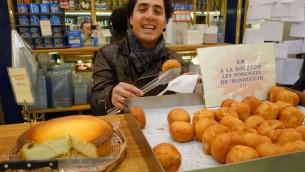 Dmitri Kahn sert des ponchkes (beignets) à la boulangerie de sa mère, rue des Rosiers, dans le quartier juif du Marais. (Crédit : Greg Scrugg/The Times of Israel)