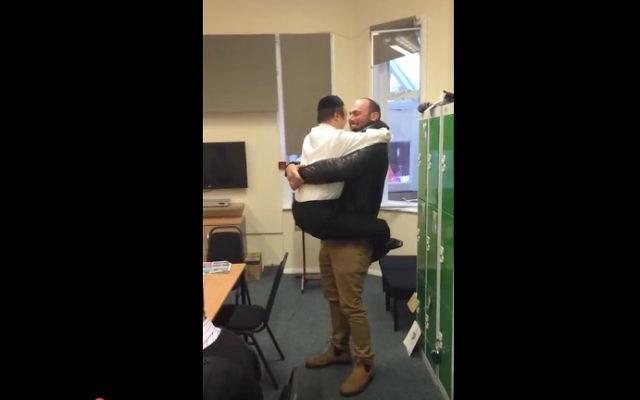 Elisha Levy (à droite) surprend un ancien étudiant à Kisharon, Londres, le 15 décembre 2015. (Crédit : capture d'écran YouTube)