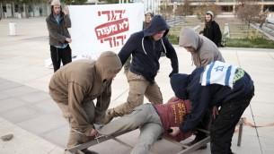 Des militants juifs de droite manifestent contre des tortures supposées du Shin Bet en rejouant les techniques présumablement utilisées par l'agence sur la place Habima de Tel Aviv, le 23 décembre 2015. (Crédit : Tomer Neuberg / Flash90)