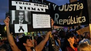 """Une femme tenant une pancarte avec le portrait du procureur Alberto Nisman à Rosario, en Argentine, le 18 Février, 2015, au cours d'une marche simultanée : """"Marcha del silencio"""" (la Marche du Silence) organisée par les procureurs argentins en mémoire de leur regretté collègue Nisman à Buenos Aires  (Crédit : AFP / NA - Agencia Cordoba)"""