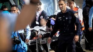 Des médecins et secouristes israéliens évacuent un garde de sécurité du tramway blessé d'un coup de coutau dans le quartier de Pisgat Zeev à Jérusalem le 10 novembre 2015 (Crédit photo: Mouammar Awad / Flash90)