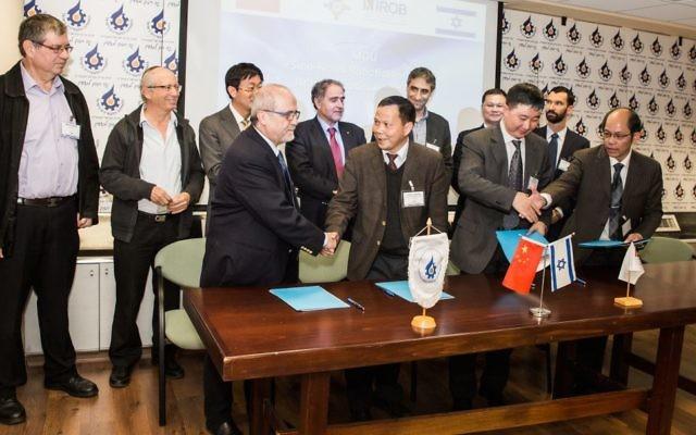 Entourés d'officiels israéliens et chinois, Zvi Shiller et Zhang Jin (centre gauche) signent un accord pour ouvrir un nouveau centre de recherche et développement robotiques en Israël. (Crédit : Autorisation)