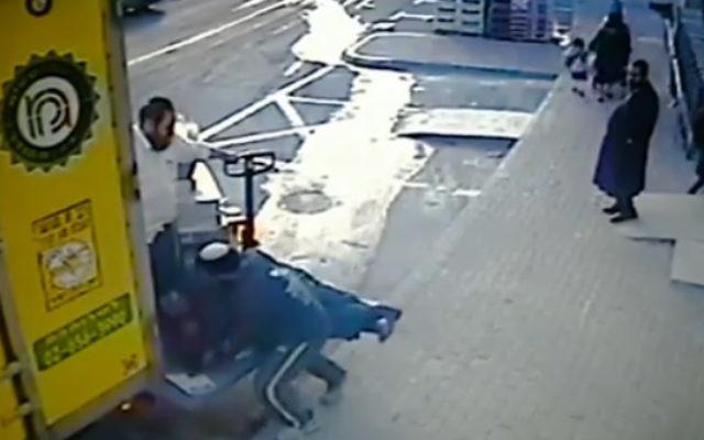 Une capture d'écran d'une vidéo montrant le propriétaire israélien d'un supermarché attaquer  son employé arabe (Crédit : Capture d'écran Walla)
