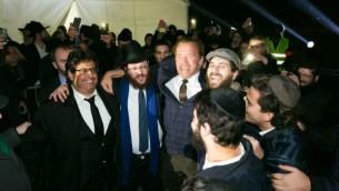 L'ancien gouverneur de Californie Arnold Schwarzenegger danse avec les rabbins Loubavitch à une cérémonie d'allumage de menorah publique au pied de la Tour Eiffel à Paris, le dimanche 6 décembre, 2015, la première nuit de la fête de huit jours. (Crédit : chabad.org/Thierry Guez)