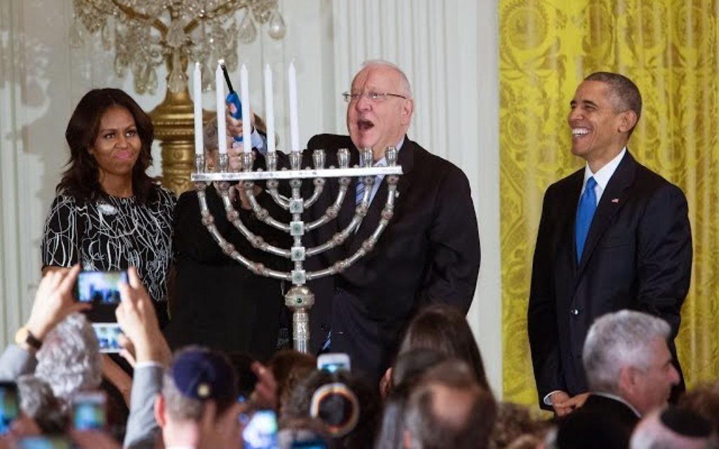 Le président Reuven Rivlin allume la menorah de Hanoukka , en présence du président américain Barack Obama, de Michelle Obama, et de Nechama Rivlin, à la Maison Blanche, le 9 décembre 2015. (Crédit : capture d'écran YouTube/The White House)