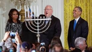 Le président Reuven Rivlin allumant la menorah de Hanoukka , en présence du président Barack Obama, de Michelle Obama, et de Nechama Rivlin, dans la East Room de la Maison Blanche à Washington, le mercredi 9 décembre 2015. (Capture d'écran YouTube / The White House)