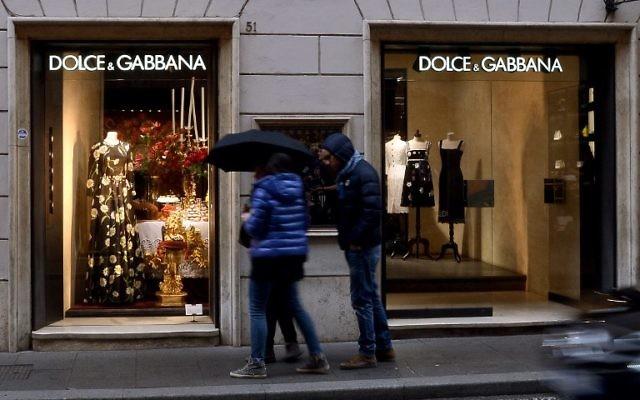 Des gens devant une vitrine Dolce e Gabbana dans le centre de la Via Condotti de Rome le 8 janvier 2016. (Crédit : AFP / FILIPPO MONTEFORTE)
