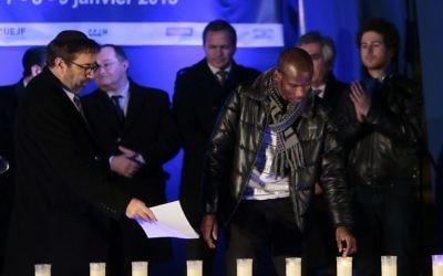 Lassana Bathily allume des bougies le 9 Janvier, 2016 près de l'Hyper Cacher,  lors d'une cérémonie organisée pour rendre hommage aux victimes de l'attentat contre le supermarché le 9 Janvier 2015 (Crédit : AFP / JACQUES DEMARTHON)