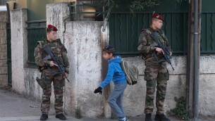 Des soldats français armés devant l'entrée de l'école juive  'La Source' à Marseille, le 12 janvier 2016. (Crédit : Boris Horvat/AFP)