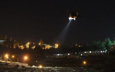 Le village palestinien de Dahriya, avec un hélicoptère de l'armée israélienne volant au-dessus de l'implantation d'Otniel, au sud de la Cisjordanie, alors que les forces de l'ordre recherchent un Palestinien suspecté d'avoir poignardé et tué Dafna Meir chez elle, le 17 janvier 2016. (Crédit : AFP/Hazem Bader)