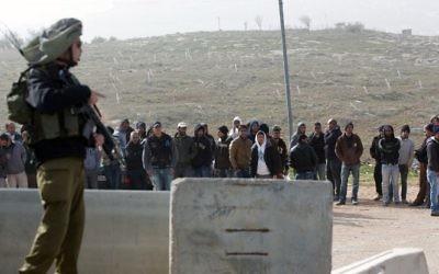 Un soldat israélien de garde pendant que les travailleurs palestiniens sont transportés en-dehors de l'implantation de Tekoa, au sud de Jérusalem, à la suite d'une attaque terroriste dans la communauté le 18 janvier 2016. (Crédit : AFP / MENAHEM KAHANA)