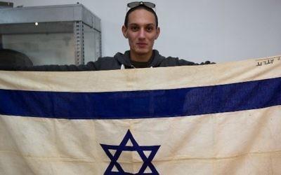 Une photo montrant un employé de  Kedem Auction House à Jérusalem montrant le drapeau du navire emblématique, le SS Exodus, le 15 novembre 2015 (Crédit : AFP / MENAHEM KAHANA)