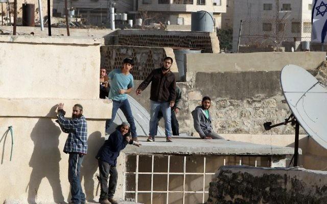 Les résidents juifs se tenant sur le toit d'un bâtiment après avoir saisi deux maisons dans le centre de Hébron, le 21 janvier 2016 (Crédit : AFP / Hazem Bader)