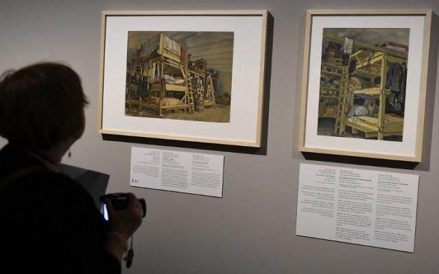 """Une journaliste devant des peintures de l'exposition """"L'art de l'Holocauste - 100 œuvres de la collection de Yad Vashem"""" à Berlin le 25 janvier 2016. (Crédit : AFP / TOBIAS SCHWARZ)"""