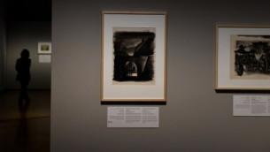 """Une femme parmi les peintures de l'exposition """"L'art de l'Holocauste - 100 œuvres de la collection de Yad Vashem"""" à Berlin le 25 janvier 2016. (Crédit : AFP / TOBIAS SCHWARZ)"""