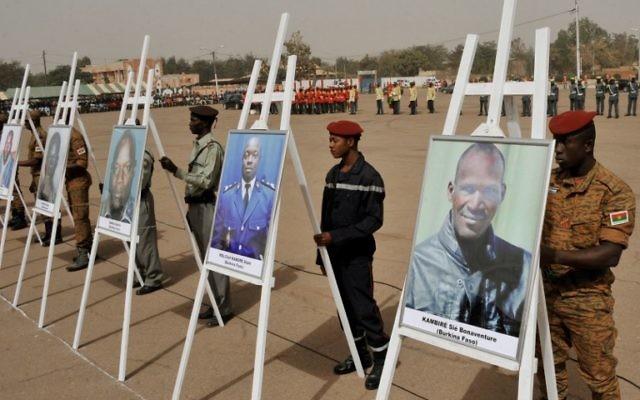 Des militaires se tenant derrière les portraits des victimes de l'attaque du 15 janvier lors d'une cérémonie de commémoration sur la place de la Nation à Ouagadougou le 25 janvier, 2016, en hommage aux victimes du 15 Janvier attaque qui a tué 30 personnes (Crédit : AFP / Ouoba AHMED)