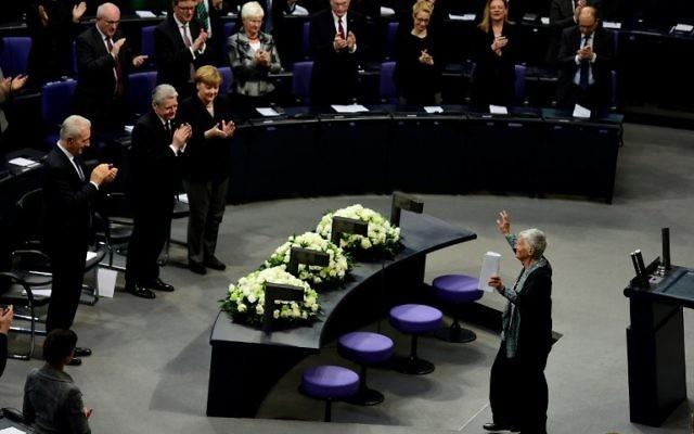 (Rangée de devant) La chancelière allemande Angela Merkel (à droite), le président Joachim Gauck (2ème à droite), le Premier ministre de Saxe Stanislaw Tillich (à gauche) applaudissant la survivante de l'Holocauste, Ruth Kluger, après son discours lors de la Journée internationale de commémoration de l'Holocauste, le 27 janvier 2016 au Parlement allemand à Berlin (Crédit : AFP / John MACDOUGALL)