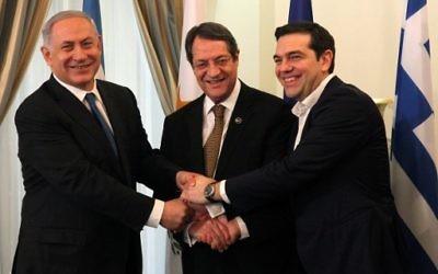 Le président chypriote, Nicos Anastasiades (au centre), le Premier ministre israélien Benjamin Netanyahu (à gauche) et le Premier ministre grec, Alexis Tsipras se serrant la main lors de leur rencontre au palais présidentiel à Nicosie, à Chypre, le 28 janvier 2016 (Crédit : POOL/AFP / Yiannis Kourtoglou)
