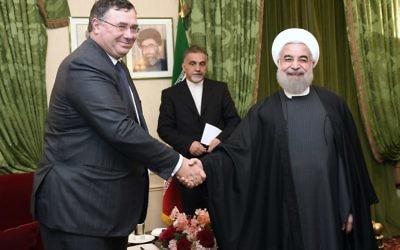Le patron du géant pétrolier français, Patrick Pouyanné (à gauche) serrant la main au président iranien Hassan Rouhani le 28 janvier 2016 durant une réunion à Paris (Crédit :  AFP PHOTO / ERIC FEFERBERG)