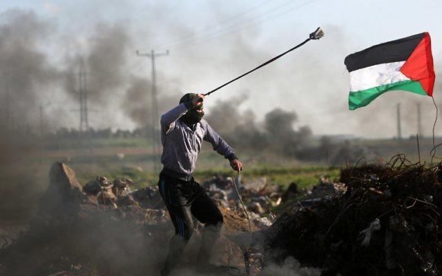 Des manifestants palestiniens ont lancé des pierres sur les forces de sécurité israéliennes lors d'affrontements près de la zone Shajaiya de la ville de Gaza le long de la frontière avec Israël, le 18 décembre 2015 (Crédit : AFP PHOTO / MAHMUD HAMS)