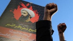 Les manifestants iraniens soulevant leurs poings en face d'un portrait de l'éminent dignitaire religieux chiite Nimr al-Nimr pendant une manifestation contre son exécution par les autorités saoudiennes, le 3 janvier 2016, devant l'ambassade d'Arabie Saoudite à Téhéran (Crédit : AFP PHOTO / ATTA KENARE