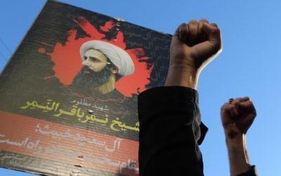 Iraniens devant un portrait du dignitaire religieux chiite Nimr al-Nimr, pendant une manifestation contre son exécution par les autorités saoudiennes, devant l'ambassade d'Arabie Saoudite à Téhéran, le 3 janvier 2016. (Crédit : Atta Kenare/AFP)