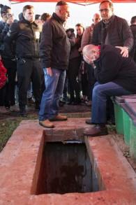 Le père et la famille d'Alon Bakal, qui a été assassiné dans une attaque à Tel-Aviv, portent le deuil à côté de sa tombe pendant son enterrement à Carmiel le 3 janvier 2016. (Crédit : AFP PHOTO / JACK GUEZ)