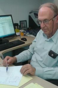 Dr Avi Ramot, le directeur du Centre israélien pour l'accessibilité, examinant les plans pour les arrêts de bus sécurisés (Crédit : Shekel)