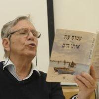 Le célèbre auteur israélien Amos Oz qui lit l'un de ses livres à Tel Aviv (Crédit : Tomer Neuberg / Flash90)