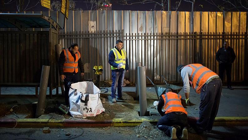 Des ouvriers israéliens et palestiniens qui placent des barrières à un arrêt de bus à Jérusalem le 20 décembre 2015, après une attaque terroriste la semaine dernière (Crédit : Yonatan Sindel / Flash90)