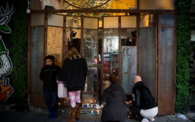 Des Israéliens allument des bougies au bar Simta sur la rue Dizengoff, dans le centre de Tel Aviv, le 2 janvier 2016. (Crédit : Miriam Alster/Flash90)