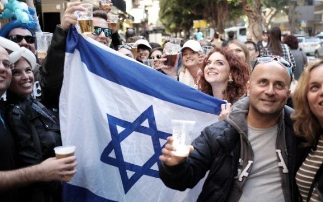 Des Israéliens assistent à une fête de rue au Bar Simta sur la rue Dizengoff à Tel-Aviv le 15 janvier 2016, dans le bar où deux Israéliens ont été tués et plusieurs autres blessés dans une fusillade le 1er janvier 2016. (Crédit : Tomer Neuberg / FLASH90)