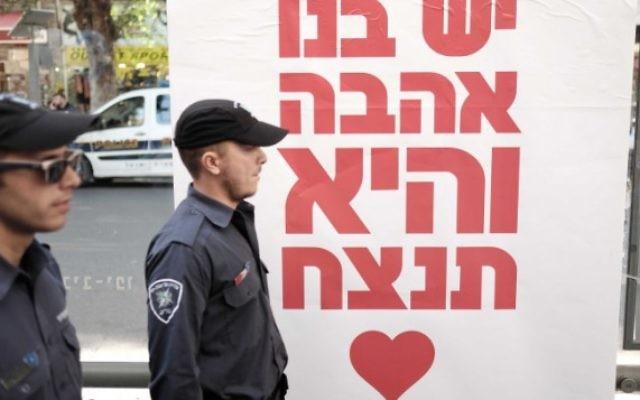 """Les policiers marchent devant une affiche où l'on peut lire : """"Nous avons de l'amour en nous, et il va gagner"""", lors d'une fête de rue le 15 janvier 2016 au bar Simta à Tel Aviv, où deux Israéliens ont été tués dans une fusillade le 1er janvier 2016. (Crédit : Tomer Neuberg / FLASH90)"""