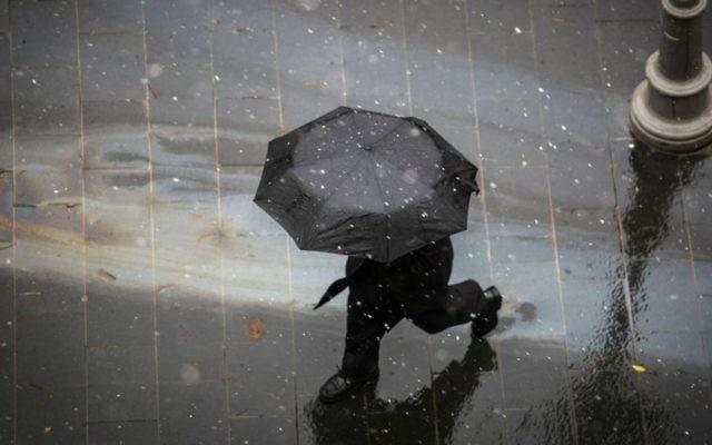 Une passant avec un parapluie dans le centre de Jérusalem tandis qu'une légère neige commence à tomber, le 25 janvier 2016 (Crédit : Hadas Parush / Flash90)