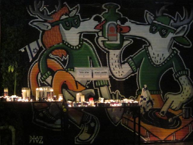 Des tables remplies avec des bougies commémoratives à la mémoire des deux victimes de l'attaque de vendredi sur la rue Dizengoff (Crédit : Eliana Block / Times of Israël)