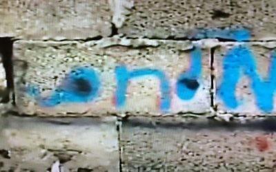 """Le nom de famille en hébreu """"Milhem"""" écrit en bleu sur le mur extérieur du dernier bâtiment dans lequel le tireur de Tel Aviv, Nashat Milhem, s'est caché à Arara avant d'être retrouvé, pourchassé et tué le 8 janvier 2016. (Crédit : capture d'écran Deuxième chaîne)"""
