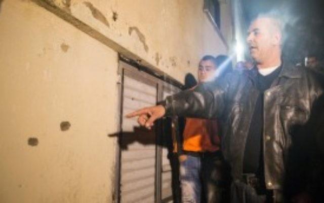 Un homme montre les impacts de balles là où les forces de l'ordre israéliennes ont abattu Nashat Milhem, qui avait tué trois personnes dans des fusillades le 1er janvier à Tel Aviv, à Arara, dans le nord d'Israël, le 8 janvier 2016. (Crédit : AFP PHOTO/JACK GUEZ)