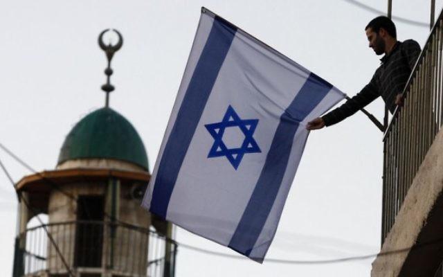Un Israélien juif brandissant un drapeau israélien près de la Vieille Ville de Jérusalem, qui a vu un afflux de résidents juifs dans des quartiers majoritairement arabes. (Crédit : Abir Sultan/Flash 90)