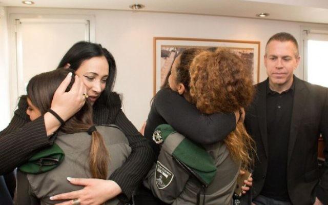 Yifat Ben-Ari (à gauche), dont le mari a été tué par une balle perdue de la police, embrasse les policières qui a accidentellement tiré sur lui pendant une attaque au couteau. (Crédit : police d'Israël)