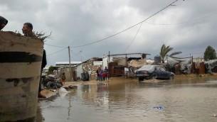 Des palestiniens près d'une route inondée à Khan Younis, dans le sud de la bande de Gaza, alors que de fortes pluies tombent, le 24 janvier 2016. (Crédit : Abed Rahim Khatib/Flash90)