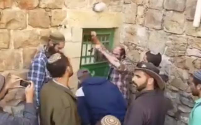 Des résidents d'implantations entrant par la force le 21 Janvier 2016 à Hébron dans des propriétés qu'ils prétendent avoir secrètement achetées (Capture d'écran YouTube)
