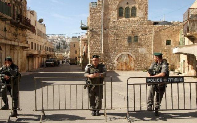 Des garde-frontières devant les  deux maisons d'où des résidents juifs ont été évacués à Hébron,  le 22 janvier 2016. (Crédit : Hazem Bader/AFP)