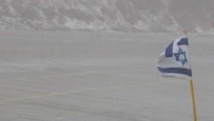Un drapeau israélien dans la tempête de neige sur le mont Hermon, dans le nord du plateau du Golan, le 31 décembre 2015. (Crédit : Basel Awidat/Flash90)