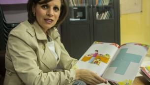 """Dalia Fadila dans l'école maternelle de Tira, avec son livre """"Où est ma famille ?"""" (Crédit : autorisation)"""
