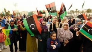 Des libyens avec leur drapeau dans un square de Tripoli, le 6 novembre 2014. (Crédit : Mahmud Turkia/ AFP)